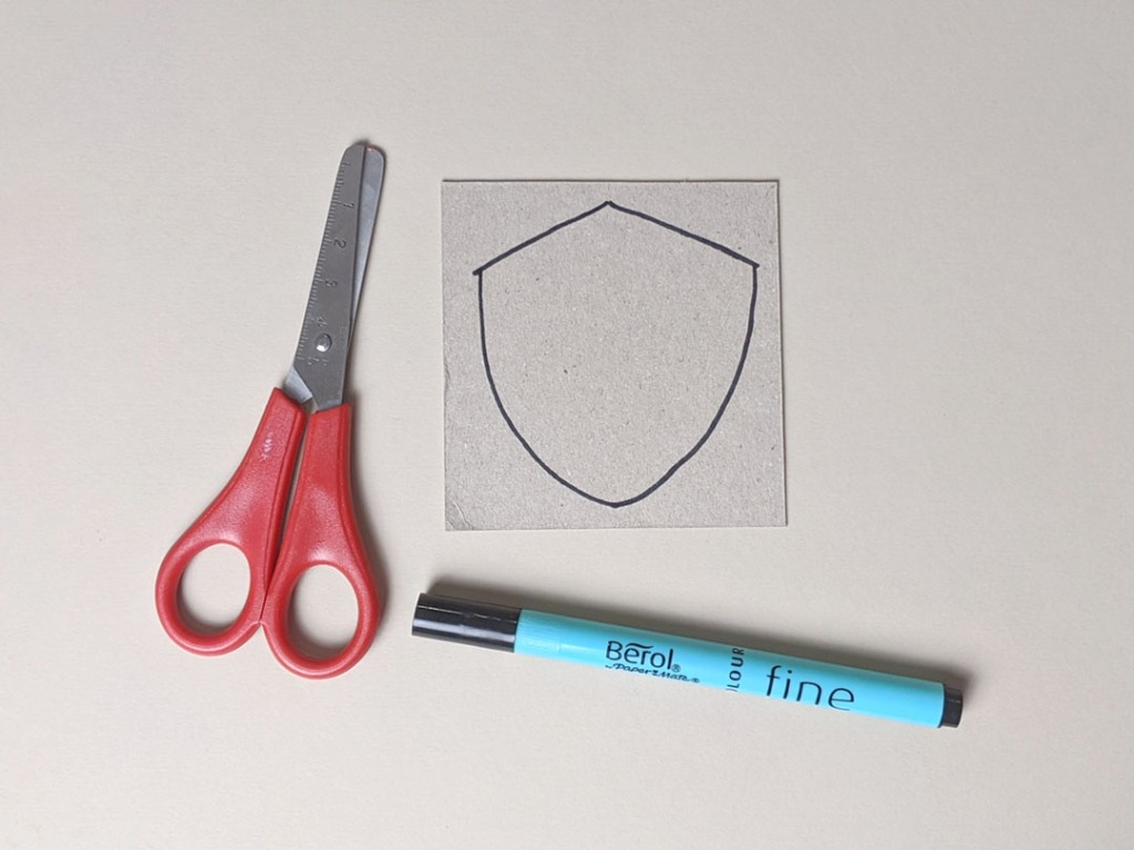 Image of a pair of safety scissors, a pen, and a piece of card.