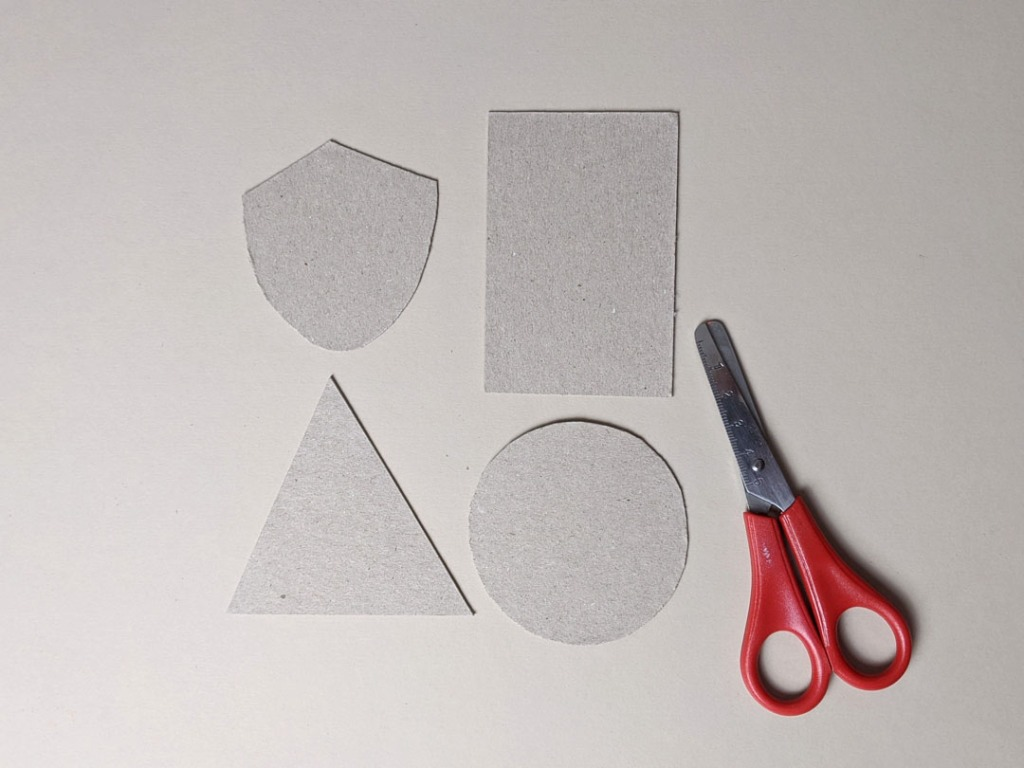 Image of a pair of safety scissors, and four shapes cut from card.  Clockwise from top left:  shield, rectangle, circle, triangle.