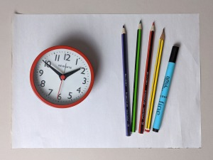 Photograph of a sheet of paper, pencils and pens, and a clock